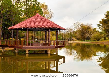 Peaceful asian garden with a wooden pavilion on a beautiful lake