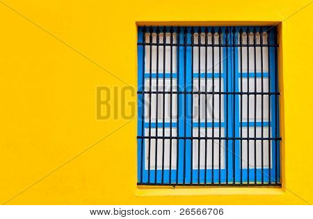 Blue window on a bright yellow wall with copyspace