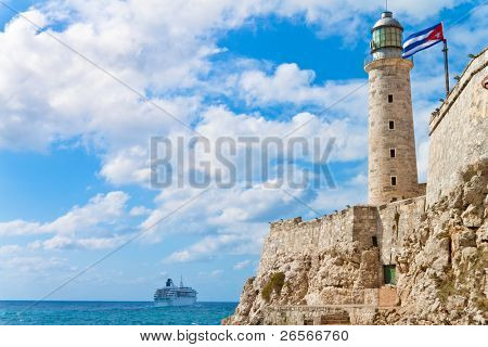 The castle of El Morro in the bay of Havana with a waving cuban flag and a tourism cruiser ship in the distance