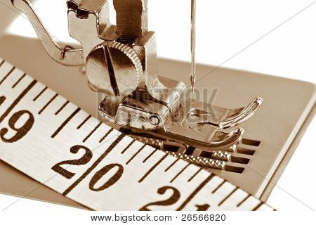Detail of a sewing machine with a measuring tape in sepia