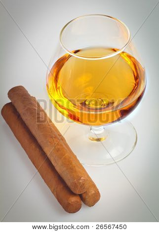 Glass of cognac, brandy or any similar alcoholic drink with cuban cigars in a vignetted background