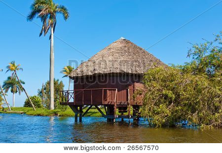 House over pillars at a lake in the cuban touristic village of Guama