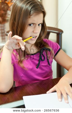 Small girl making a funny face and working on her school project at home