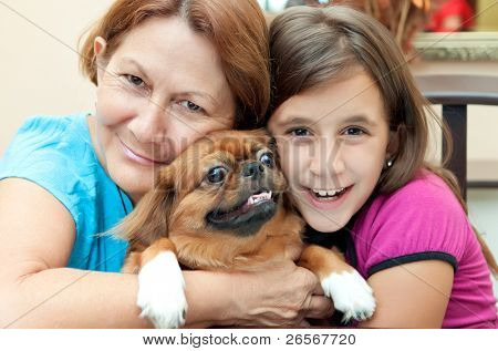 Latin grandmother and granddaughter hugging the family dog