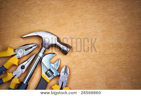 Set of tools over a wood panel with space for text