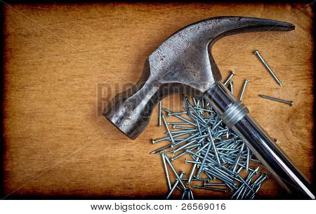 Hammer head and nails on a  wooden panel with space for text