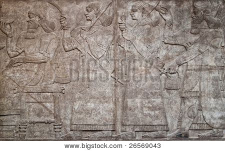 Ancient assyrian clay relief depicting a row of warriors with weapons and text written in cuneiform writing