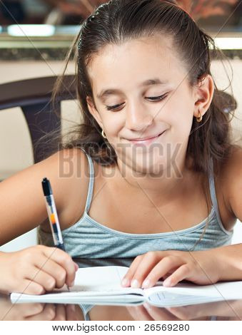 Adorable small latin girl working on her school project at home