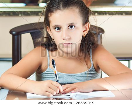 Adorable hispanic girl studying at home