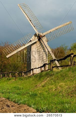Very old wooden fence and old windmill on a green field near wood