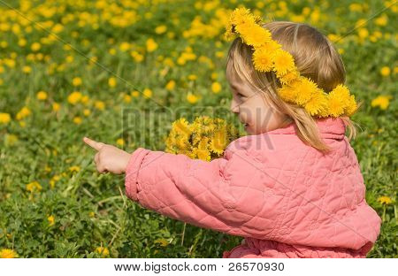 Portrait of the little girl with a wreath from dandelions on a head