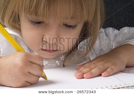 Beautiful little girl is drawing with crayons on paper