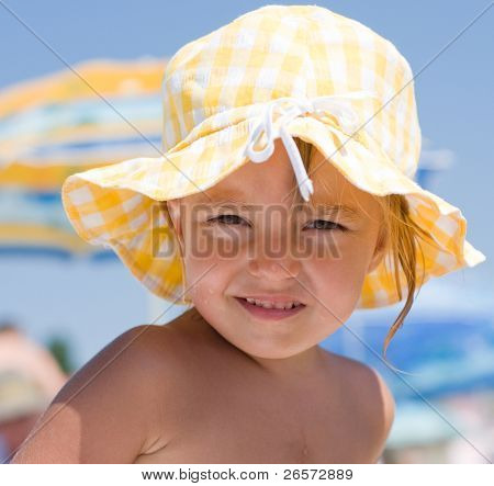 Little girl with sun hat on beach