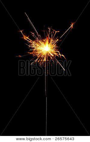 Burning christmas sparkler isolated on black background