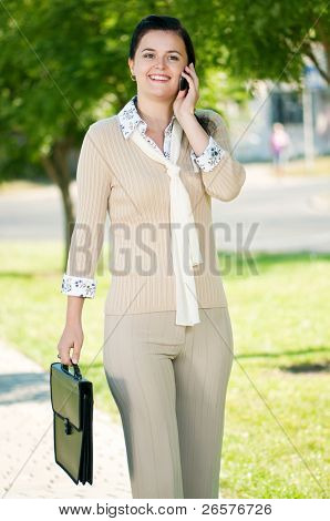 Portrait of smiling modern young business woman with briefcase and mobile cell phone in park outdoors