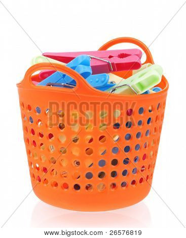 Pile of clothes-pegs of different colors on a white background
