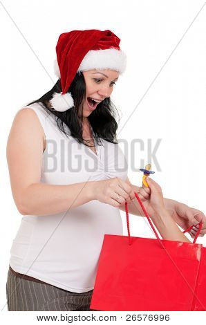 Portrait of a pregnant woman in santa hat holding a shopping bags over white background