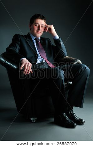 young businessman sitting in black chair, tonned in blue-green tint