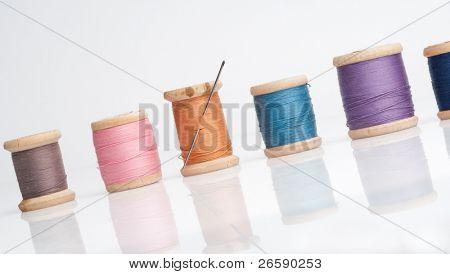 Aguja de coser e hilos. Aislado en blanco.