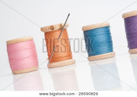 Sewing needle and threads. Isolated on white.