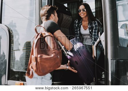 poster of Smiling Young Couple Boarding On Travel Bus. Handsome Man And Beautiful Woman Carrying Luggage To Bu