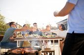 leisure and people concept - happy friends toasting drinks at barbecue party on rooftop in summer poster
