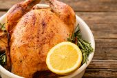 Whole Roasted Chicken With Lemon And Rosemary On A Black Plate. Rustic Style. Christmas Concept. Chr poster