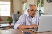 Senior man working with laptop at home. Old man using computer at home sitting on chair and looking  poster