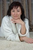 picture of blinders  - Smiling female lying on a white carpet - JPG
