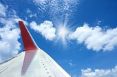 Red Aircraft Wing With Sunbeam On Blue Sky. poster