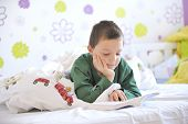 stock photo of little boy  - Young boy in his bed reading a book - JPG