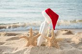 Pair Of Starfish With Santa Hat On Message In A Bottle In Beach Sand poster