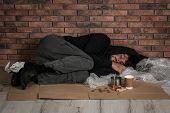 Poor Man Sleeping On Floor Near Brick Wall poster