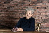 Poor Elderly Woman Counting Coins At Table poster