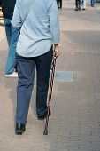 Elderly Woman Walking Down The Street With Walking Stick. Old Woman Walk Alone Down The Street With  poster