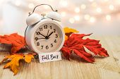 Fall Back Daylight Saving Time Concept With White Clock And Autumn Leaves, Soft Bokeh Background On  poster