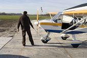 stock photo of ultralight  - Pilot pulls small ultralight airplane from hangar - JPG
