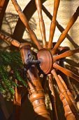 A Closeup Of A Very Old Wheel  And Spokes Of A Hand Crafted Spinning Wheel poster