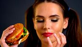Woman bite big hamburger. Girl eat fast food and lick your fingers . How to save lipstick while eati poster
