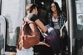 Smiling Young Couple Boarding On Travel Bus. Handsome Man And Beautiful Woman Carrying Luggage To Bu poster