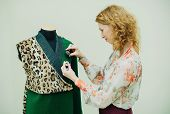 Beautiful Young Woman Sews Designer Coat. Leopard Print Coat And Green. poster