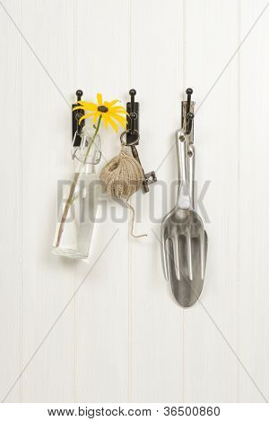 Garden tools with Rudbeckia flower in vintage glass bottle hanging on shed door