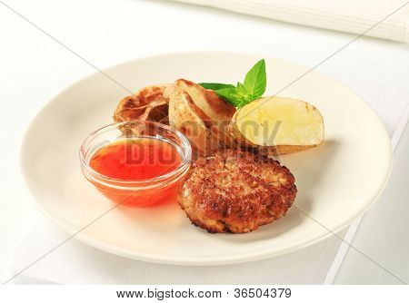 Hamburger, American potatoes and a bowl of tomato dressing