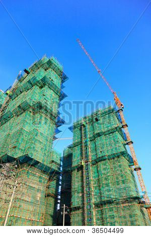 Crane and scaffolding with netting under blue sky  in a construction site