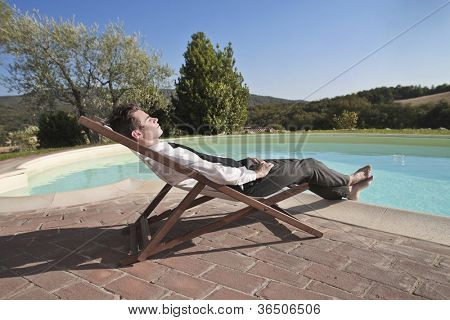 Young businessman relaxing on a deckchair by a swimming pool