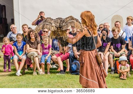 STARA LUBOVNA, SLOVAKIA - AUGUST 26: female falconer performing with eagle-owl bird during Falconry Show in Stara Lubovna, August 26 2012, Stara Lubovna, Slovakia