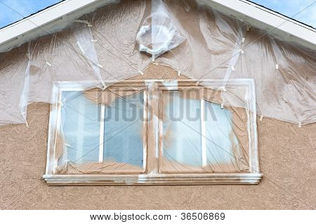 Ein Haus wird neu gestrichen werden und ist Painstakenly mit Plastikplanen zum Schutz der Gebiete von Pai maskiert