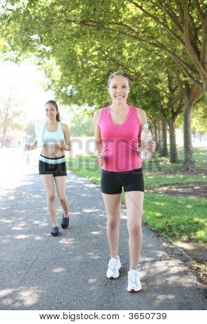 Pretty Sisters Jogging In Park