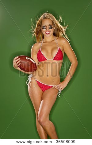 A blonde model posing with a football in a studio environment