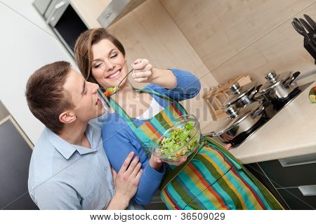 Woman feeds her husband with salad with vegetable in the modern comfortable kitchen